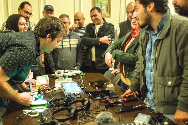 Artist Gene Felice leaning over a table with tech gadgets surrounded by participants of American Arts Incubator Egypt