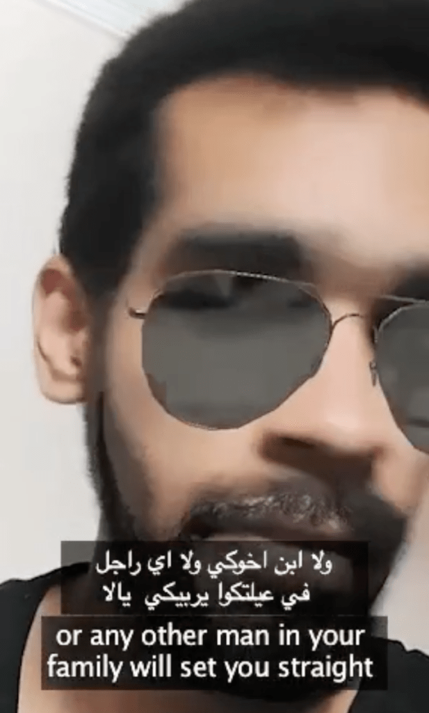 """Screenshot of a selfie video of a man with an AR filter of aviator sunglasses and a beard. Closed captioning reads in both Arabic and English, """"or any other man in your family will set you straight."""""""