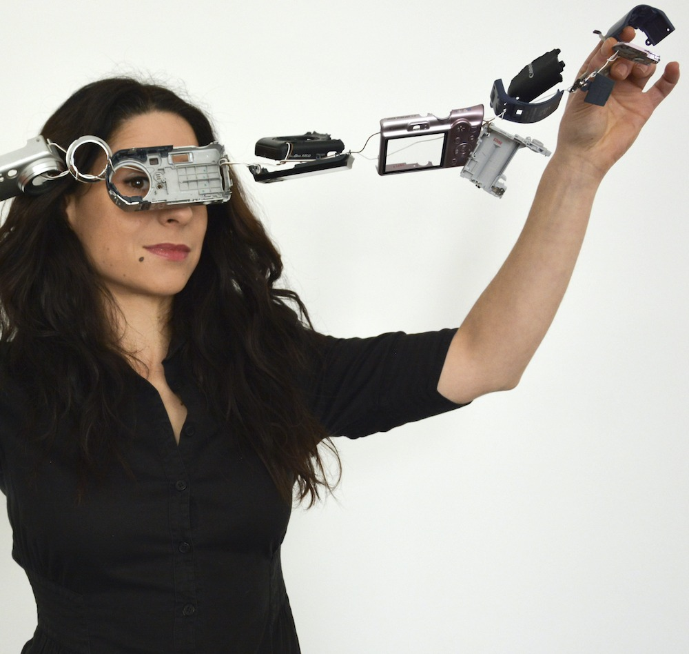 Headshot of Patricia J Reis holding up a string of disassembled electronics and office supplies